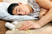 image of home remedy  - Teenager sleeps near the scattered Pills on the Bed at the Home - JPG