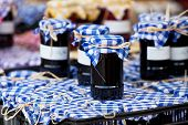 foto of jar jelly  - Many preserving jars with dark jam in a market. Horizontal shot