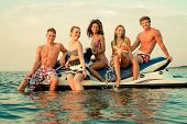 stock photo of ski boat  - Group of multi ethnic friends sitting on a jet ski - JPG