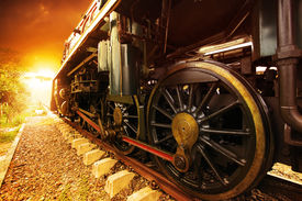 stock photo of train-wheel  - iron wheels of stream engine locomotive train on railways track perspective to golden light forward use for old and classic period land transport and retro vintage style background - JPG