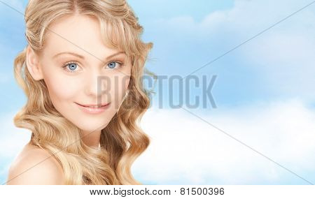people, beauty, body and skin care concept - beautiful woman face and hands over blue sky background