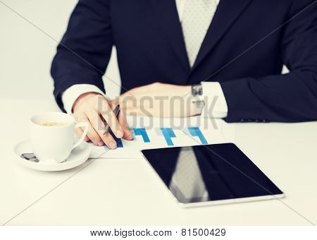 man with tablet pc, cup of coffee and graphs