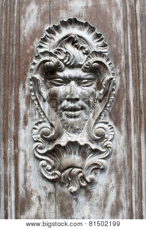 Face Shaped Decoration On A Wooden Door