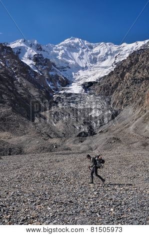 Hiker walking across scenic Engilchek glacier with picturesque Tian Shan mountain range in Kyrgyzstan
