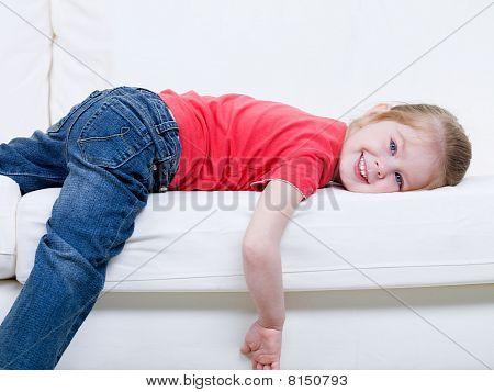 Little Girl Lying On The Sofa