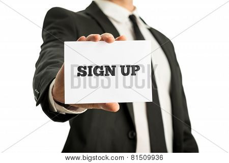 Businessman Holding Up A Business Card Saying Sign Up