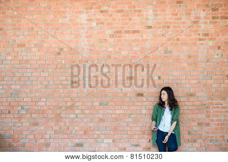 Young Asian Woman Wear Green Coat Stand In Front Of Brick Wall Backround