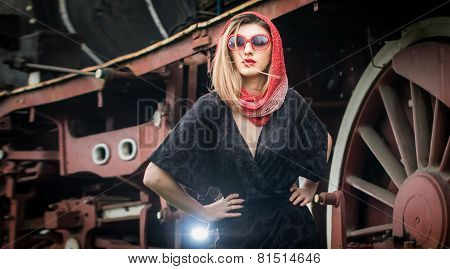 Sexy attractive girl with red head scarf and sun glasses posing on the platform in front of  train
