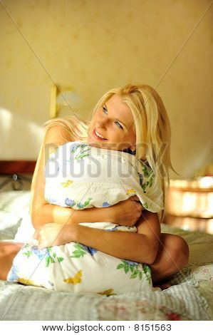 Young Beautiful Woman Sitting With A Pillow On Her Bed In The Morning