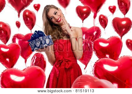 beautiful girl in red dress on Valentines day with gift and red heart shaped balloons