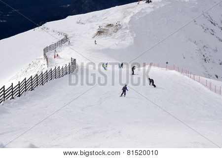 Skiers and snowboarders going down the slope at ski resort.