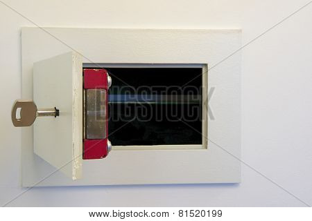 Open wall mounted safe box with a key.