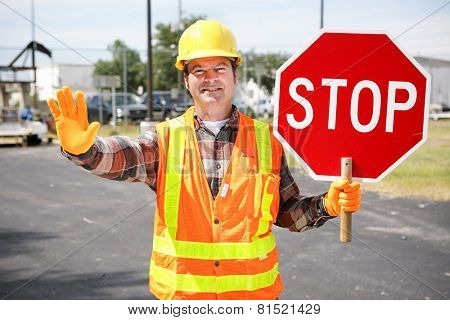 Friendly construction worker in the road holding up a stop sign.