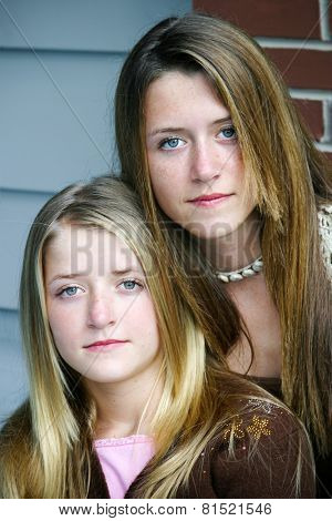 Portrait of beautiful teenage sisters, serious expressions.