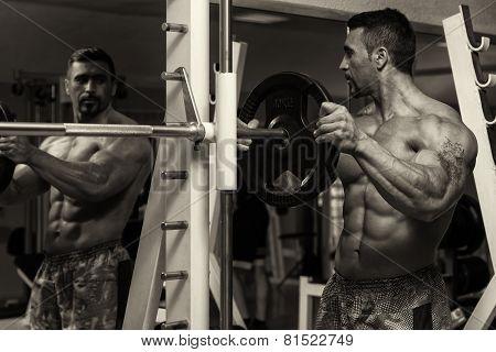 Bodybuilder Putting Weights On Bar In Gym