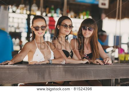 Three beautiful girls in a bar on the beach, on the ocean.