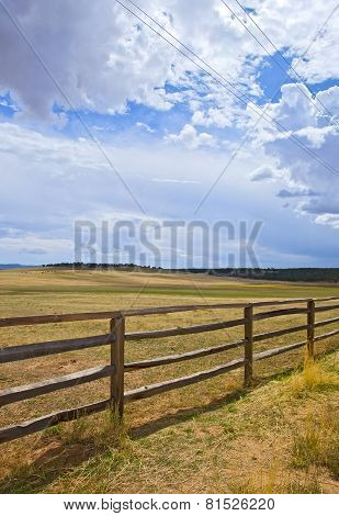 Wooden fence on a rural farm pasture fields on a beautiful sunny day