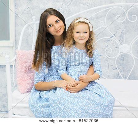 Portrait Beautiful Mother And Daughter In Dress Together On The Bed At Home