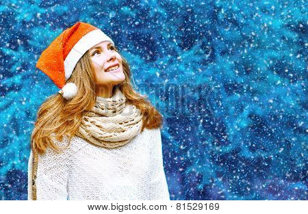 Christmas And People Concept - Happy Woman In Red Hat Make A Wish Near Tree In Winter Snowy Day