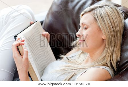 Charming Woman Reading A Book Sitting On A Sofa