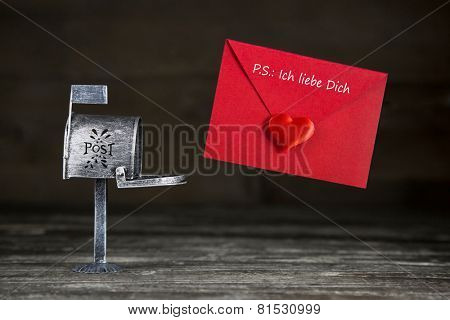 Love letter in red color with heart for valentines day goes to a letter box. Text in german letters for