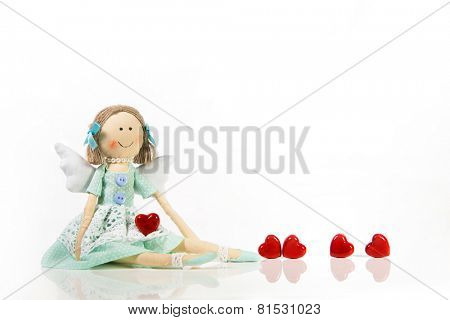 Isolated handmade doll like an angel with red hearts.