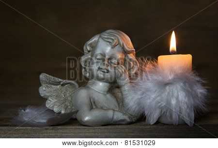 Sad angel with burning candle for bereavement or mourning background