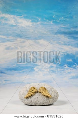 Golden angel wings with stone on blue heaven background for spiritual concepts.