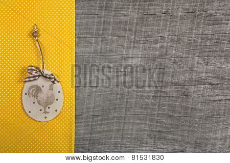 Easter decoration with cock label hanging on a yellow dotted fabric on wooden background.