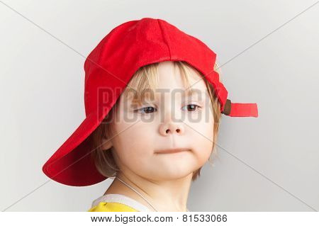 Studio Portrait Of Funny Baby Girl In Red Baseball Cap