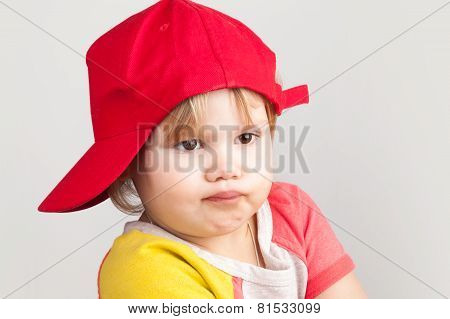 Studio Portrait Of Funny Confused Girl In Red Baseball Cap