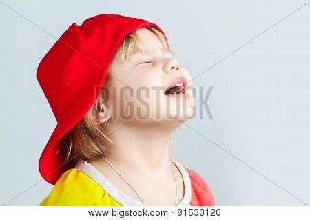 Studio Portrait Of Happy Baby Girl In Red Baseball Cap