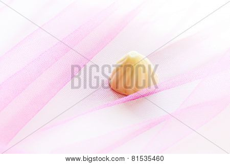 A close up of single white chocolate in colorful background