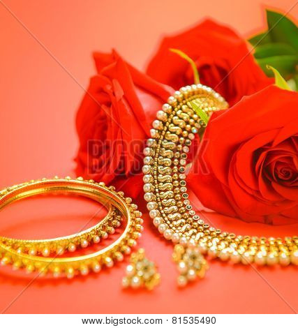 Traditional indian gold necklace and bangles set with rose flower on red background.