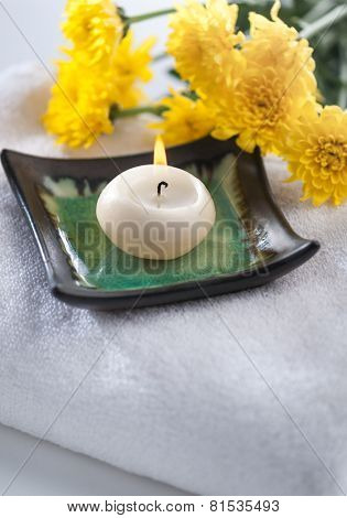 Scented candle with natural flowers placed on white towel - spa still life