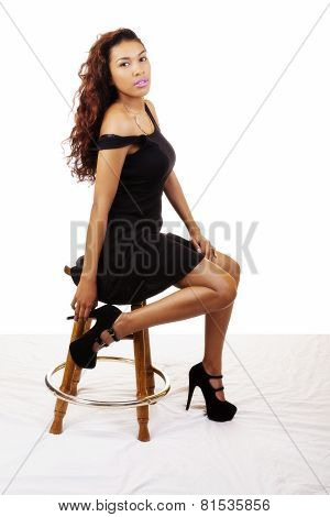 Young Latina Woman Sitting On Stool Dress