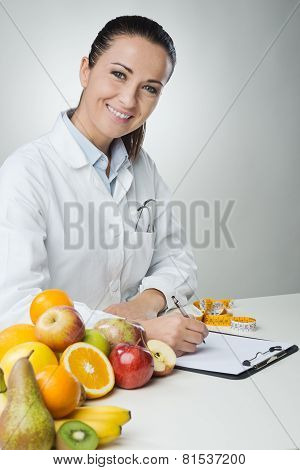 Smiling Nutritionist Writing Medical Records