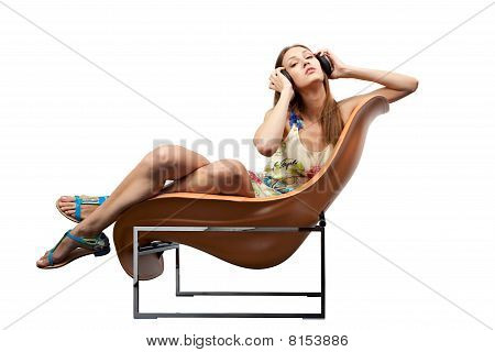 Young adult sitting in the chair listening to music