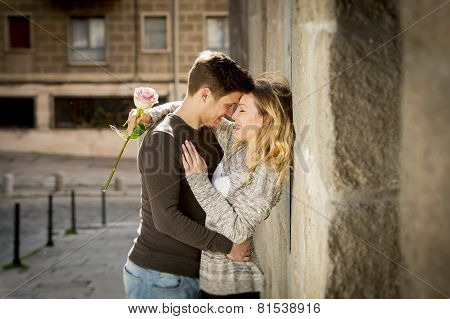 Candid Portrait Of Beautiful European Couple With Rose In Love Kissing On Street Alley Celebrating