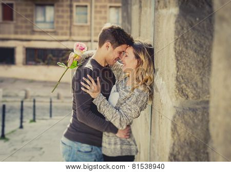 Candid Portrait Of Beautiful European Couple With Rose In Love Kissing On Street Alley Celebrating V
