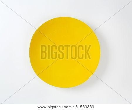 Rimless round plate with yellow glaze