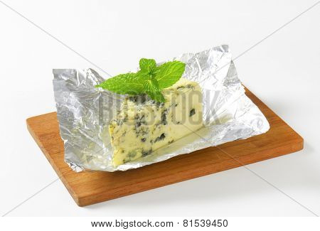 unpacked blue cheese from aluminum foil, served on the wooden cutting board