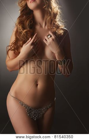 Studio shot of curvy nude woman posing in jewelry