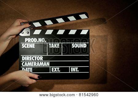 Movie clapper in female hand on wooden background