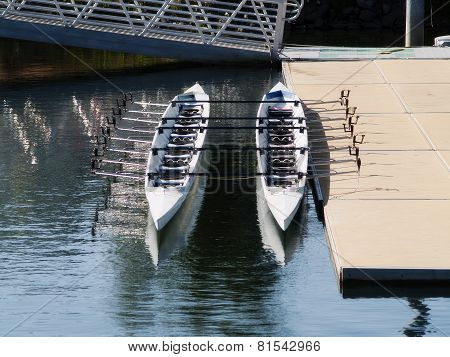 Two Empty Rowing Shells Sitting At Dock Side