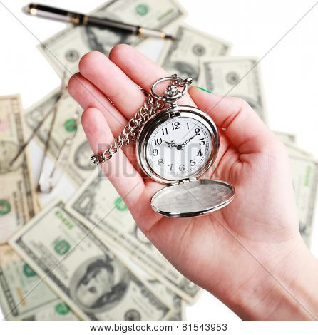 Silver pocket clock in hand on money background. Time is money concept