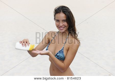 Woman Showing Suncream At The Beach