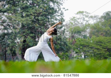 Beautiful Woman Practicing Yoga In The Park.