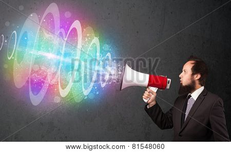 Handsome guy yells into a loudspeaker and colorful energy beam comes out