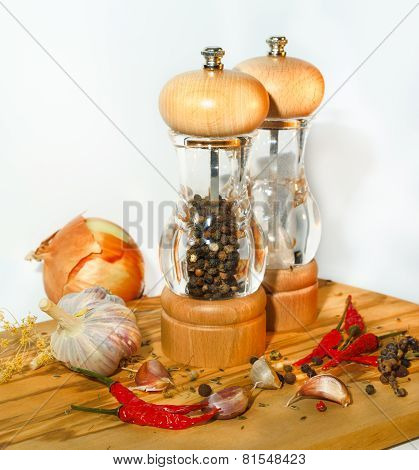 Salt And Pepper Mill With Ingredients Around On Wooden Cutting Board